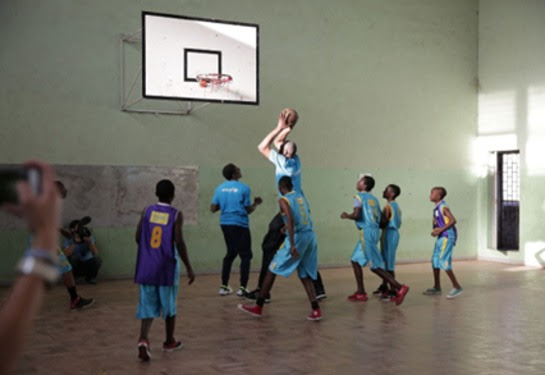 Dikembe Mutumbo goes for a basket while playing with local players at a school in Maputo, Mozambique.