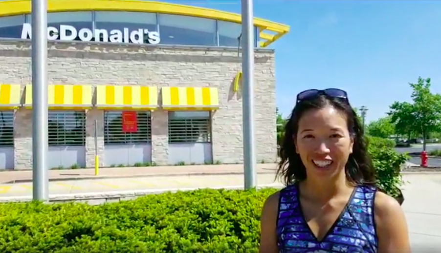 Dr Elaine Leung standing in front of a McDonalds restaurant smiling with a blue sky