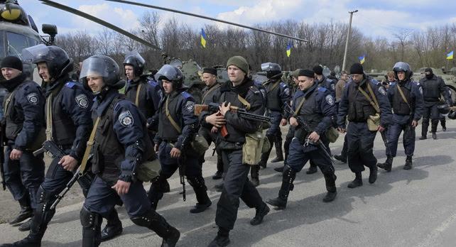 Los miembros del Ministerio del Interior de Ucrania pasan junto a un helicóptero militar MI-8 y vehículos blindados de transporte de personal en un puesto de control cerca de la ciudad de Izium, el este de Ucrania.