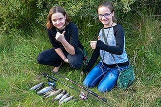 Two girls are shown giving a thumbs-up sign as they display a limit brook trout catch.