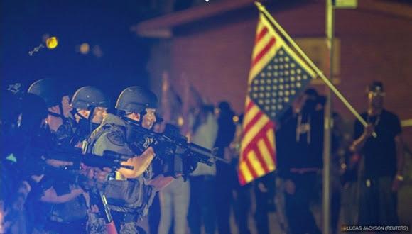 - Lucas Jackson (REUTERS) Un oficial de Policía apunta su arma contra los manifestantes. Los disturbios durante la noche han dejado 31 detenidos.