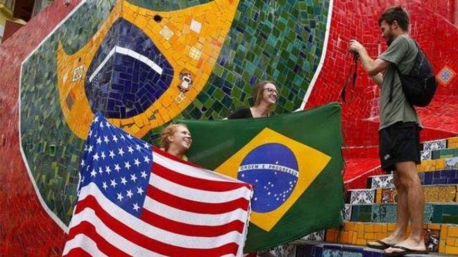Mulheres com bandeiras dos EUA e do Brasil