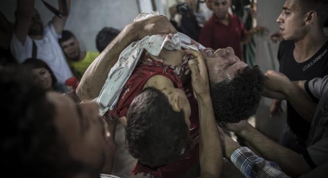 En el hospital Al Shifa, un hombre palestino sujeta el cuerpo sin vida de su hermano pequeño, muerto en un bombardeó naval isralí en el puerto de Gaza el pasado miércoles.