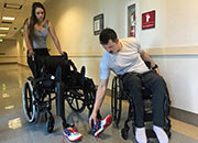 Veteran Brandon Myers removes his shoes from a wheelchair he used to harness an exoskeleton walking device