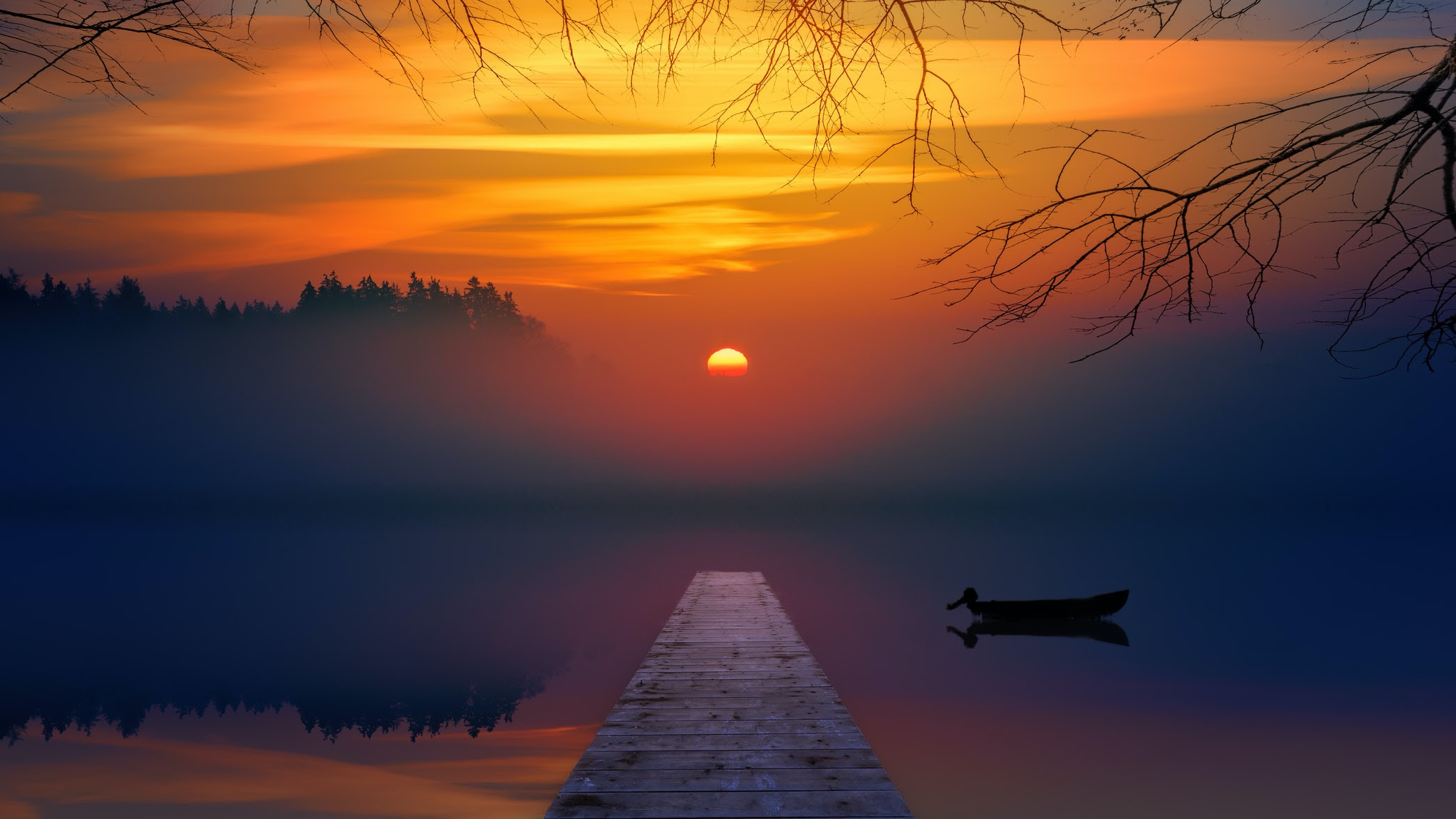 orange sunset in the mist over a lake with a dock and small rowboat