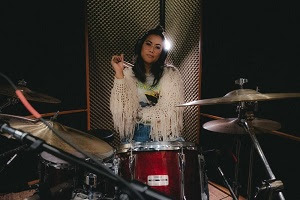 Image of a girl sitting behind a drum set