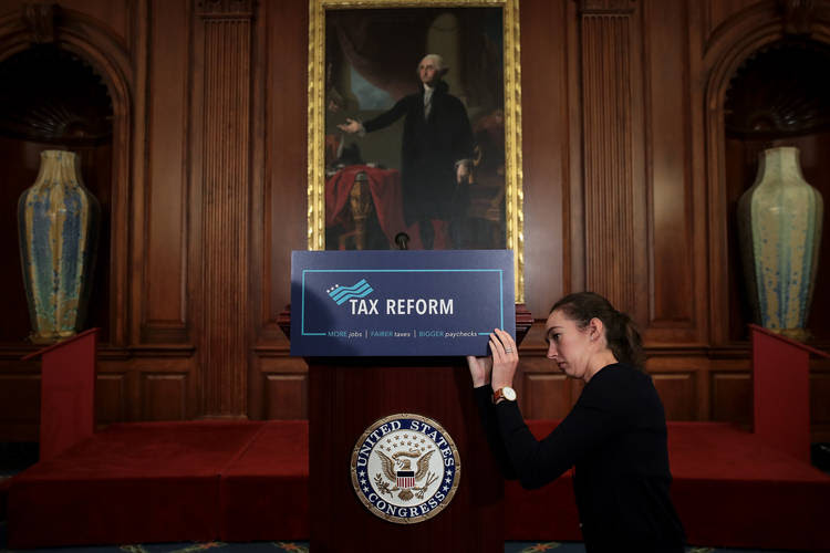 A staff member sets the stage before a news conference where Republican lawmakers announced their plans to overhaul the tax code. (Drew Angerer/Getty Images)