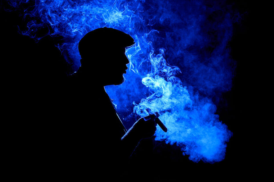 When you learn photography, you can take beautiful pictures like this, using a flash and colored lights. This example photo shows the backlit silhouette of a man smoking a cigar.