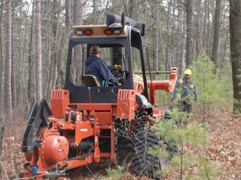 A vibratory plow is used to dig trenches to separate oak roots and stem the spread of oak wilt