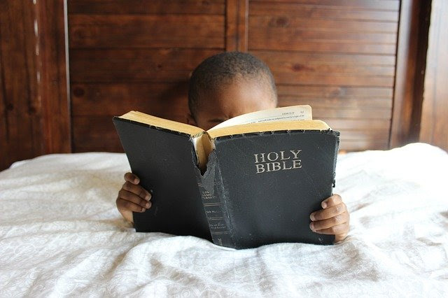 child reading Bible in bed