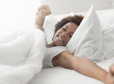 Image of a woman waking up from a restful sleep.