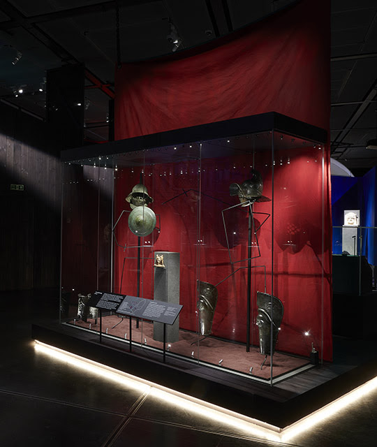 Inside 'Nero: the man behind the myth' showing gladiators' armour and helmets on display against a red background.
