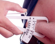 Person having their body fat measured near their waist with a caliper.