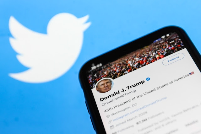 President Trump's Twitter account on a smartphone screen with the Twitter logo in the background