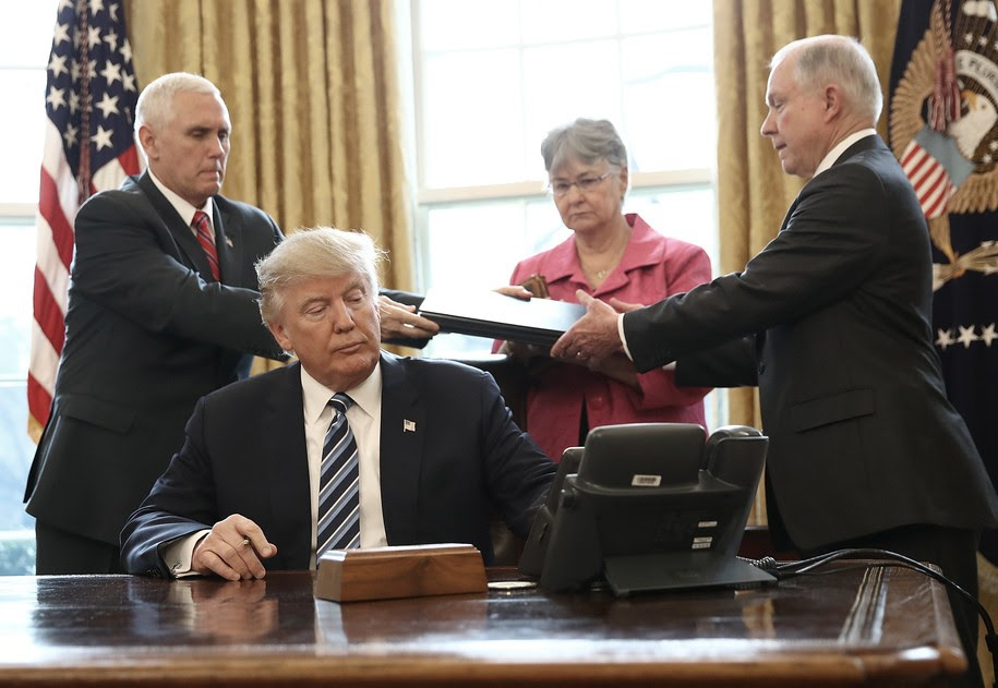 WASHINGTON, DC - FEBRUARY 09:  U.S. Vice President Mike Pence (L) hands three executive orders to newly sworn in Attorney General Jeff Sessions (R) for U.S. President Donald Trump to sign in the Oval Office of the White House February 9, 2017 in Washington, DC. Prior to signing the three executive orders, Trump participated in the swearing in ceremony for Sessions. Also pictured is Session's wife Mary (2nd R) (Photo by Win McNamee/Getty Images)