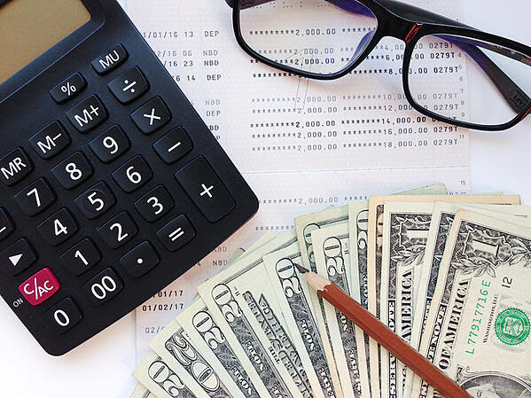Un par de anteojos, una caculadora y billetes sobre un documento financiero