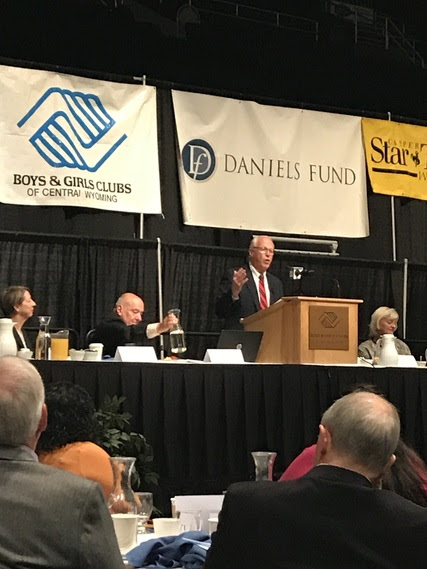 Peter Wold speaks from a podium on the stage at the Boys and Girls Club of Central Wyoming's Back-a-Kid Breakfast in the Casper Events Center.