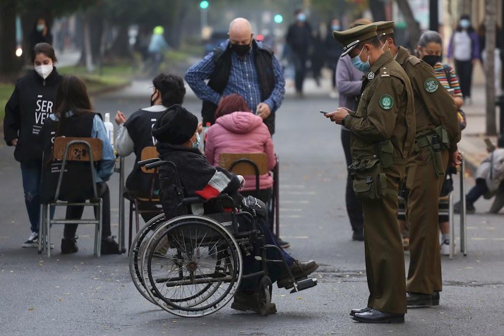 Un policía consulta la documentación de un hombre en silla de ruedas que acude a votar  en las elecciones locales y constituyentes, en el liceo de Aplicación, en la comuna de Santiago centro, en Santiago de Chile. EFE/ Elvis González
