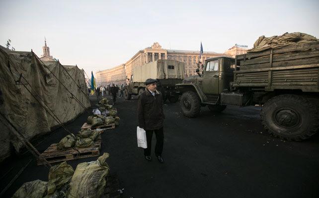 Un hombre pasea por la plaza de la Independencia, en ruinas por los enfrentamientos y tomada por las 'Fuerzas de Autodefensa'.