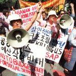 Des représentantes d'agricultrices venues du Laos, d'Indonésie, du Vietnam, de Malaisie, de Corée du Sud, du Japon et de Thaïlande manifestent contre le Fonds Monétaire International (FMI) et la Banque Mondiale devant le siège de la Bank of Thailand à Bangkok le 13 août 1999. (Crédits : AFP PHOTO/Pornchai KITTIWONGSAKUL)