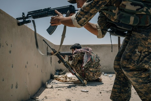 SDF soldiers take aim at a minaret, where they think an ISIS sniper is positioned on the western edge of Raqqa, Syria. (Alice Martins for The Washington Post)