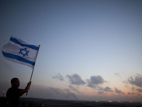 A man stands with an Israeli flag on a hill overlooking the Gaza Strip on July 20, 2014. (Photo by Lior Mizrahi, Getty Images)