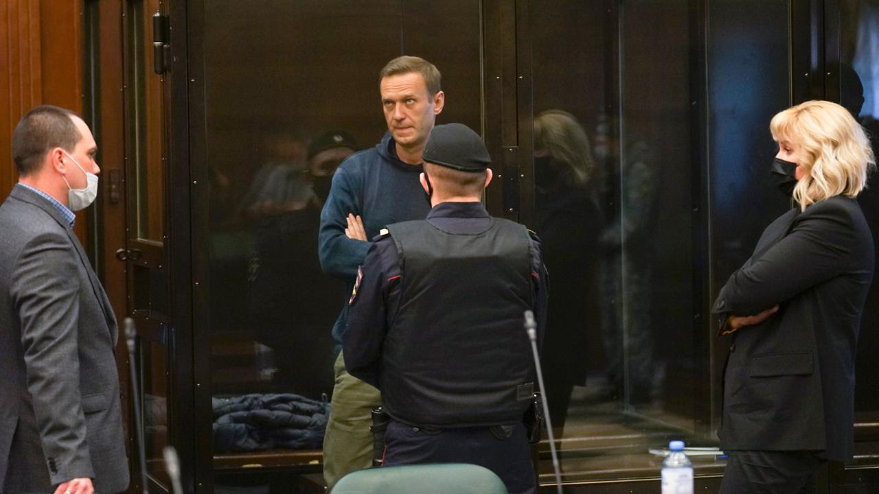 In this handout photo provided by Moscow City Court Russian opposition leader Alexei Navalny, center, stands in a glass cage during a hearing in the Moscow City Court, Feb. 2, 2021.