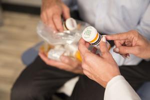 Doctor and patient reviewing prescription bottle labels