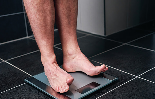 The legs of a man as he weighs himself on a bath scale.