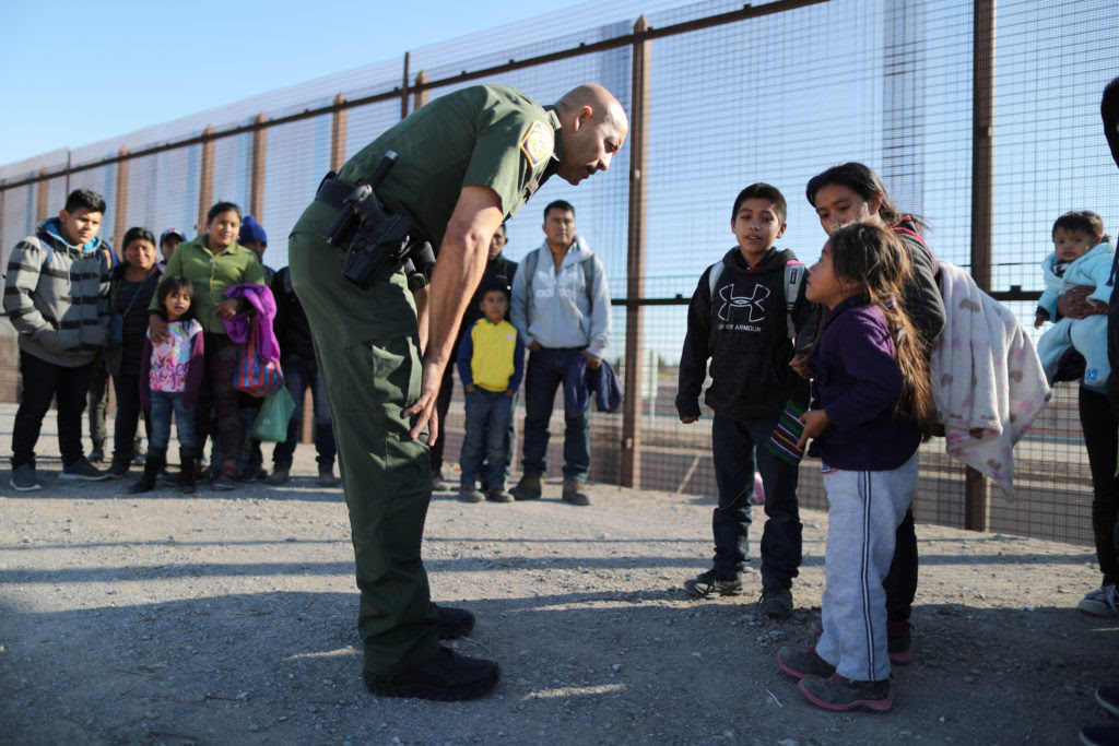 Border patrol agent talking with immigrant families