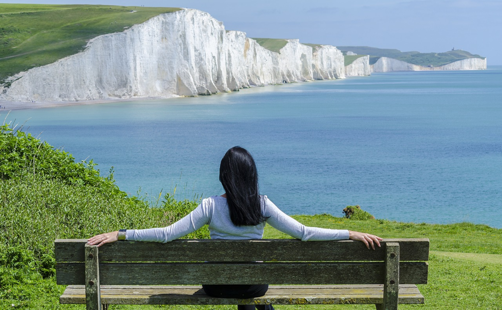 Young Lady Sat On Bench By Dover Cliffs