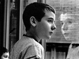 Foto in bianco e nero di profilo di ragazzo davanti a un vetro che riflette la sua immagine