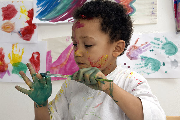 Paint-covered child holding paintbrush, surrounded by children's art
