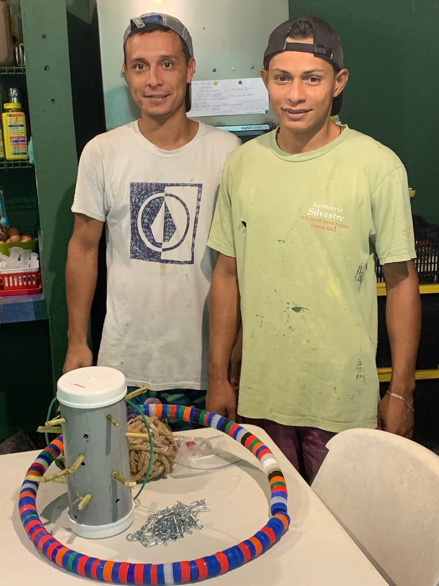 Two young men look into the camera with a table of enrichment in front of them