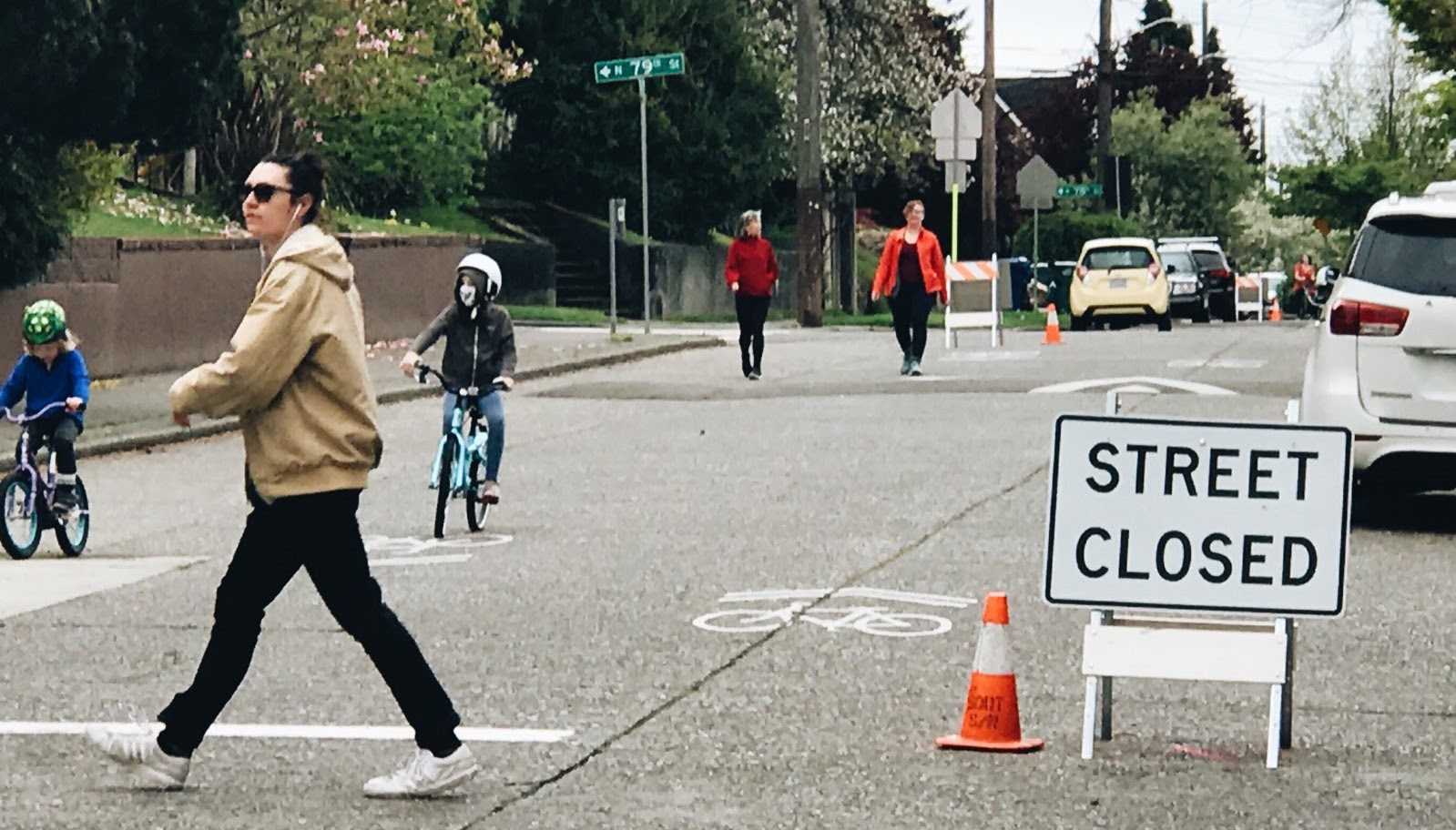 People walk and bike down the middle of a street in front of an A-frame sign that says