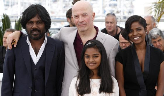 From left, actor Jesuthasan Antonythasan, director Jacques Audiard, actress Claudine Vincent Rottiers and actress Kalieaswari Srinivasan pose for photographers during a photo call for the film Dheepan, at the 68th international film festival, Cannes, southern France, Thursday, May 21, 2015. (AP Photo/Lionel Cironneau)