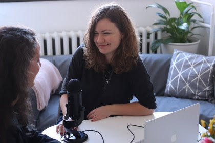 a an image of two women talking with microphone between them