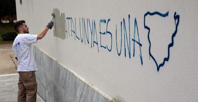 Un operario de la brigada de limpieza borran una pintada en el colegio electoral situado en el Centro Cultural Mira-sol de San Cugat donde ha votado el cabeza de lista de Junts pel Sí, Raül Romeva. /EFE