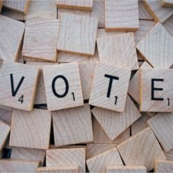 the word VOTE spelled out with wooden scrabble game tiles