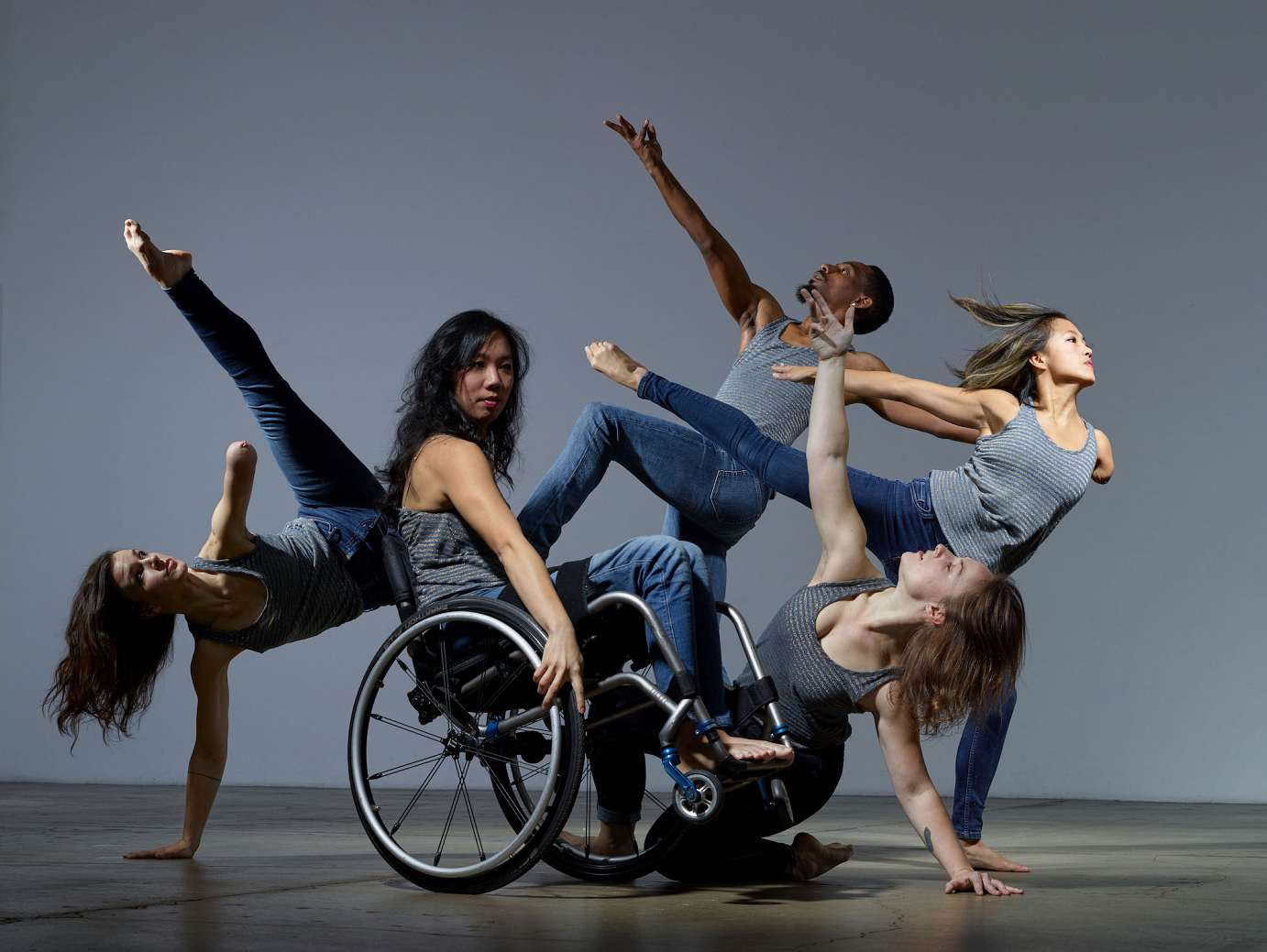 Five dancers, with and without disabilities, against a blue background. Four dancers with outstretched arms and legs surround the fifth dancer who is leaning back with her wheelchair.