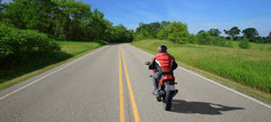 Motorcycle rider wearing a helmet riding down a road