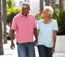 Senior couple walking along the street together.