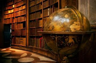 vintage globe in front of bookshelves