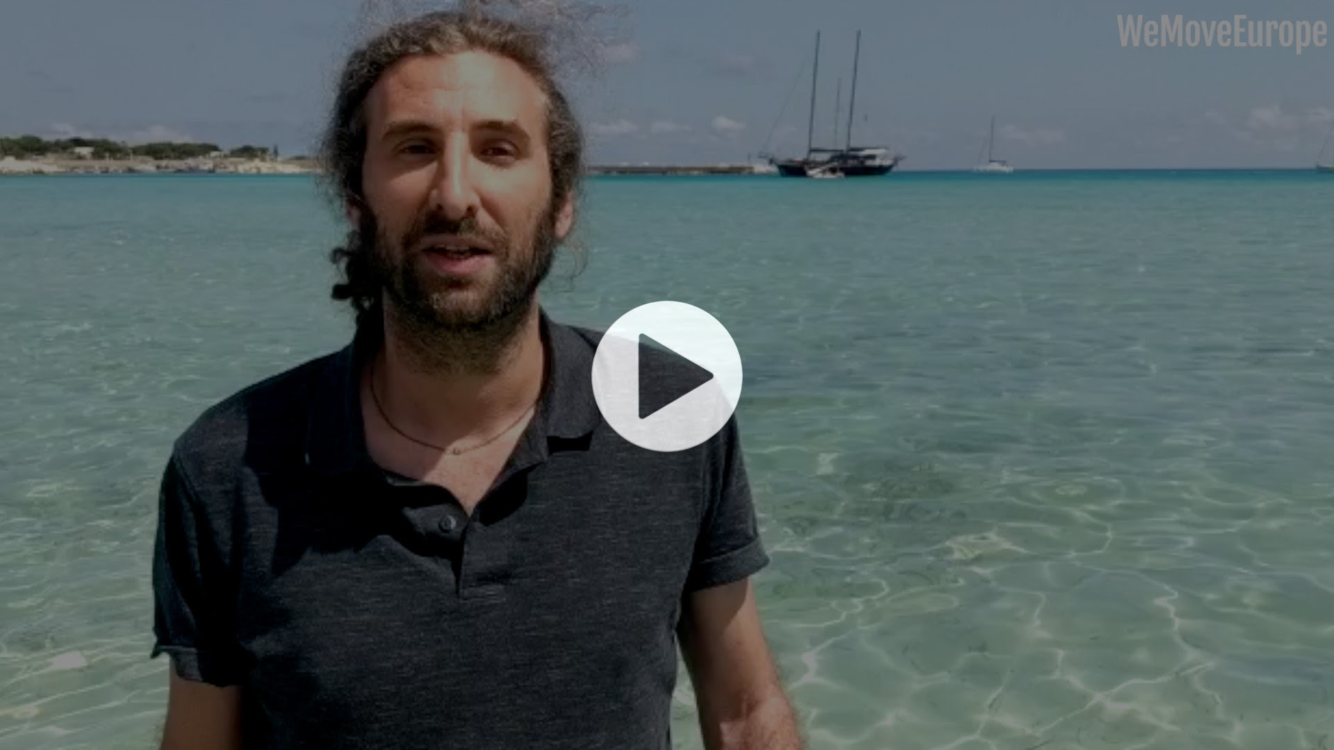 Man stands to left of image, standing in front of blue ocean, play button over top