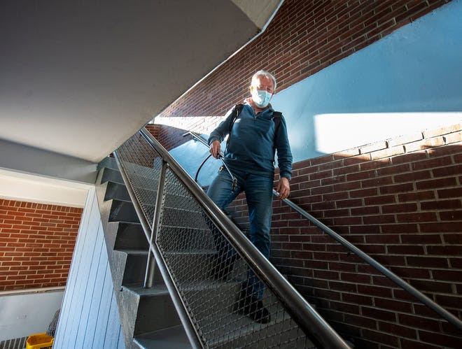Maintenance employee Mike McCafferty, of Bristol, disinfects the railings inside the stairwell at St. Michael the Archangel.