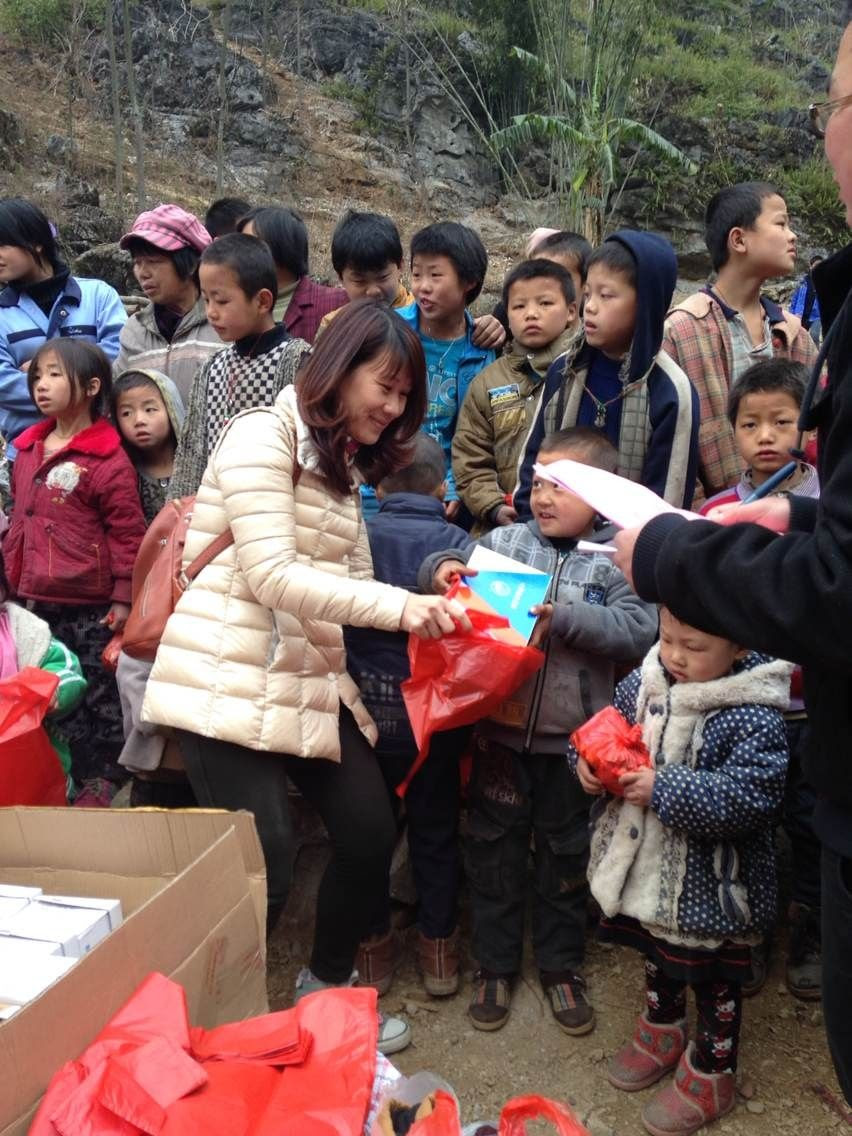 Xiaoling Mai giving out shoes and clothes to the Lin Wang Students