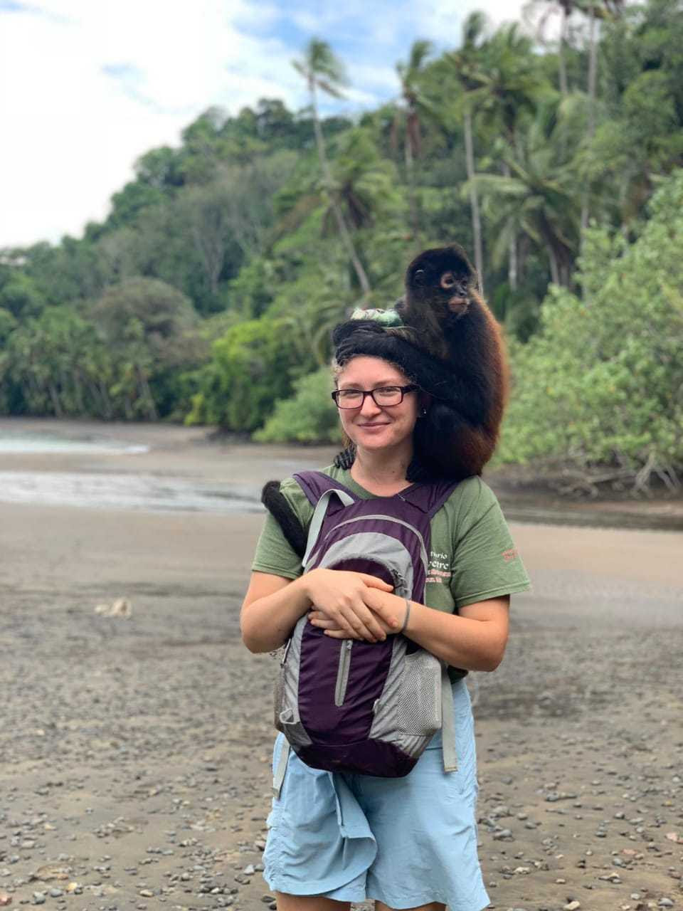 Young woman on beach with rainforest in background with spider monkey on her shoulders