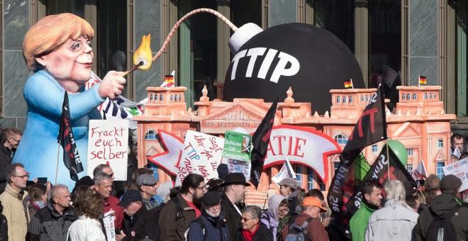 Un muñeco que representa a la canciller alemana, Angela Merkel, encendiendo 'la bomba TTIP', en la manifestación de Berlín contra el acuerdo comercial que negocia la UE con EEUU. EFE / EPA / JOERG CARSTENSEN