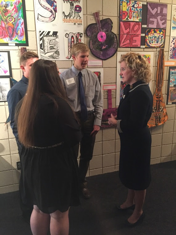 Superintendent Balow visits with three high school students in the lobby of the Cheyenne Civic Center, where student art is displayed on the wall.