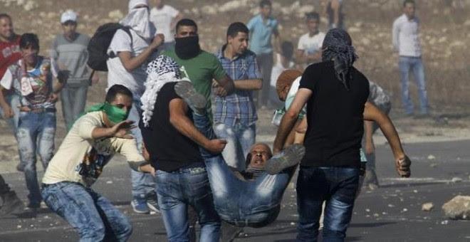 Manifestantes palestinos cargan con un compañero herido por disparos israelíes en una manifestación en el checkpoint de Howara, cerca de la ciudad de Nablus, Cisjordania.- EFE/EPA/ALAA BADARNEH